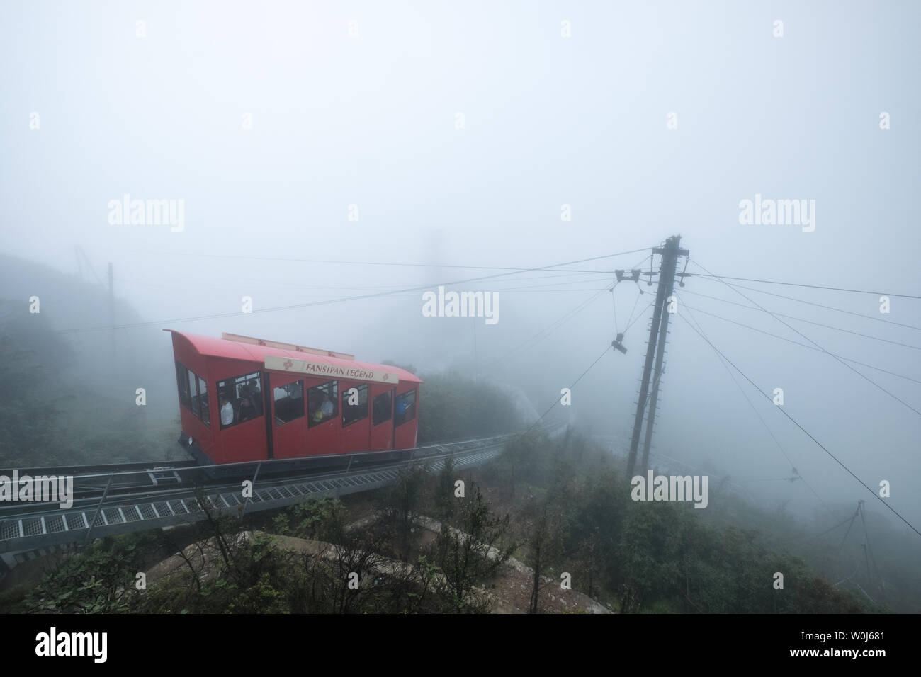 Sapa, Vietmam - Sep 08 2017 :  Red tram retro style run to the top hill with passenger on foggy day at Fansipan Legend - Stock Image