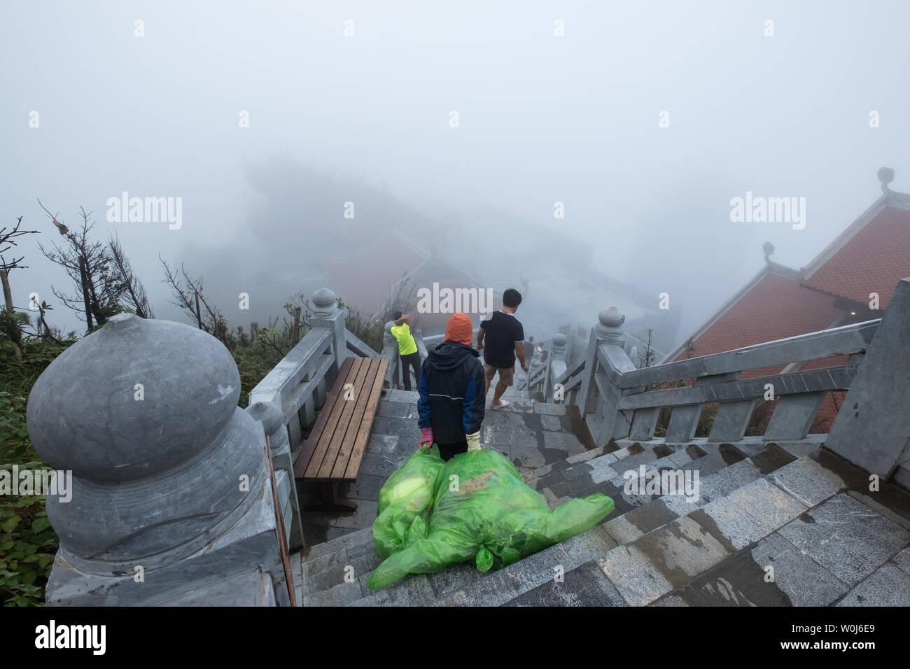 Sapa, Vietnam - Sep 08 2017 : Staff man walking down stair with dragging big garbage bag to leave - Stock Image