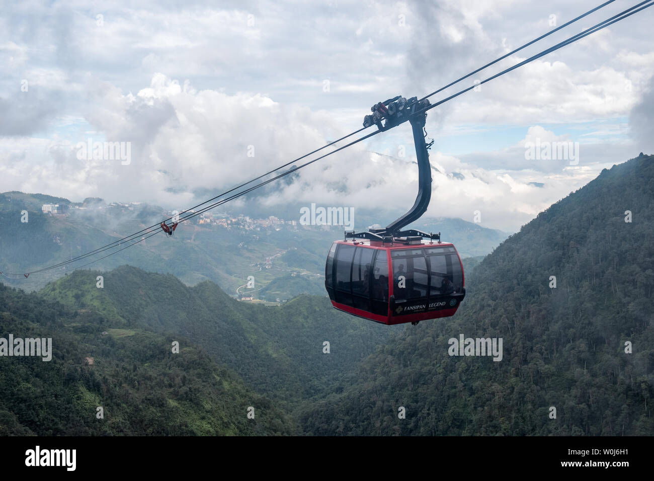 Sapa, Vietnam : Sep 08 2017 : Tourists sitting red cable car sightseeing Sapa village in valley through of fog - Stock Image