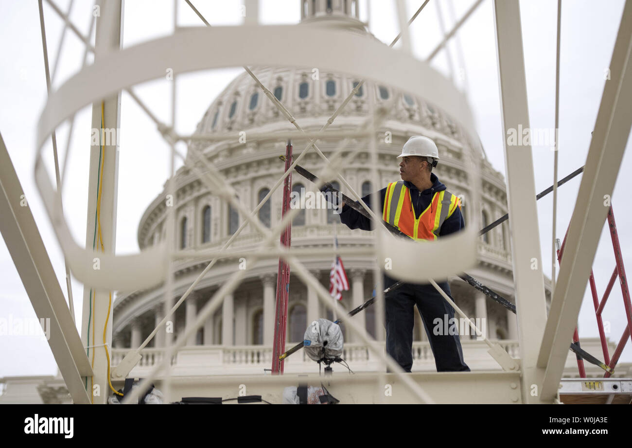 A construction worker works on the center media riser as work continues on the West Front of the Capitol in preparation of the Presidential Inauguration, at the U.S. Capitol Building in Washington, D.C. on December 8, 2016. Donald Trump will be sworn-in as Presidential on January 20, 2016. Photo by Kevin Dietsch/UPI - Stock Image