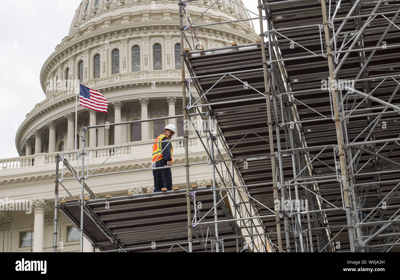 A construction worker walks on a media riser as work continues on the West Front of the Capitol in preparation of the Presidential Inauguration, at the U.S. Capitol Building in Washington, D.C. on December 8, 2016. Donald Trump will be sworn-in as Presidential on January 20, 2016. Photo by Kevin Dietsch/UPI - Stock Image