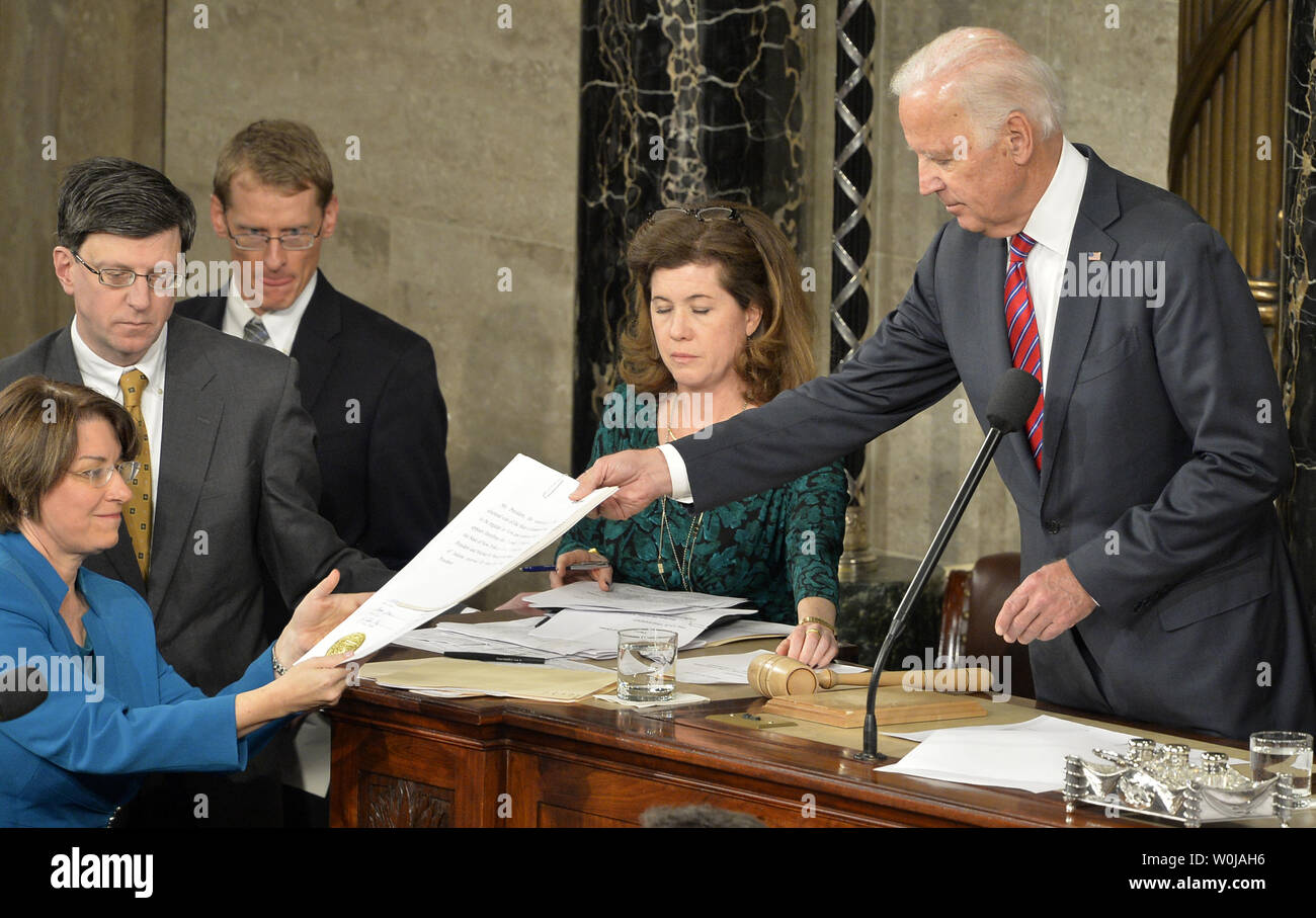 Vice President Joe Biden (R) hands a state vote to Sen. Amy Klobuchar (D-MN) as they preside over the procedure to count and validate the votes of the Electoral College on the floor of the House at the U.S. Capitol, January 6, 2017, in Washington, DC. The procedure, established by the Constitution, finalized Donald J. Trump and Mike Pence as the president and vice president.                 Photo by Mike Theiler/UPI - Stock Image