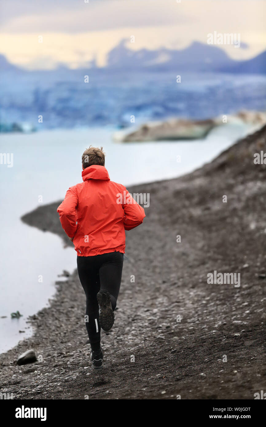 Runner man trail running training for run in beautiful nature landscape. Fit male athlete jogging and cross country running by icebergs in Jokulsarlon glacial lake in Iceland. Stock Photo