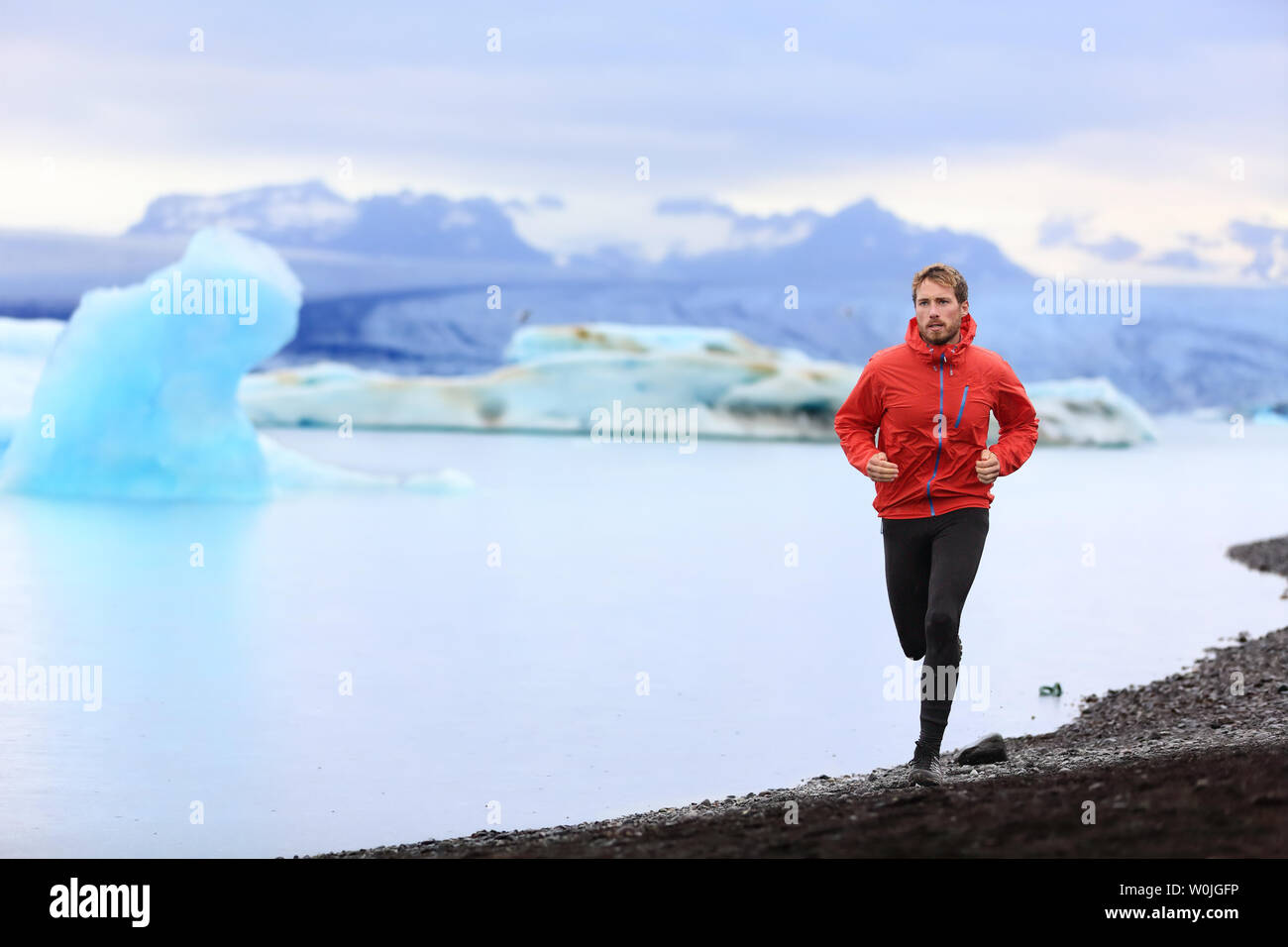 Running man. Trail runner training for marathon run in beautiful nature landscape. Fit male athlete jogging and cross country running by icebergs in Jokulsarlon glacial lake in Iceland. Stock Photo