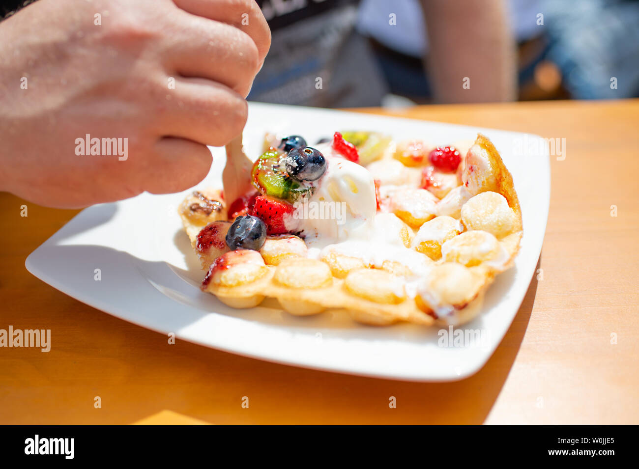 Trend pastry Bubble Waffles (Egg Waffles, Hong Kong cakes) with ice cream and fresh fruits. Strawberries, kiwi, bilberries, strawberry sauce on white - Stock Image
