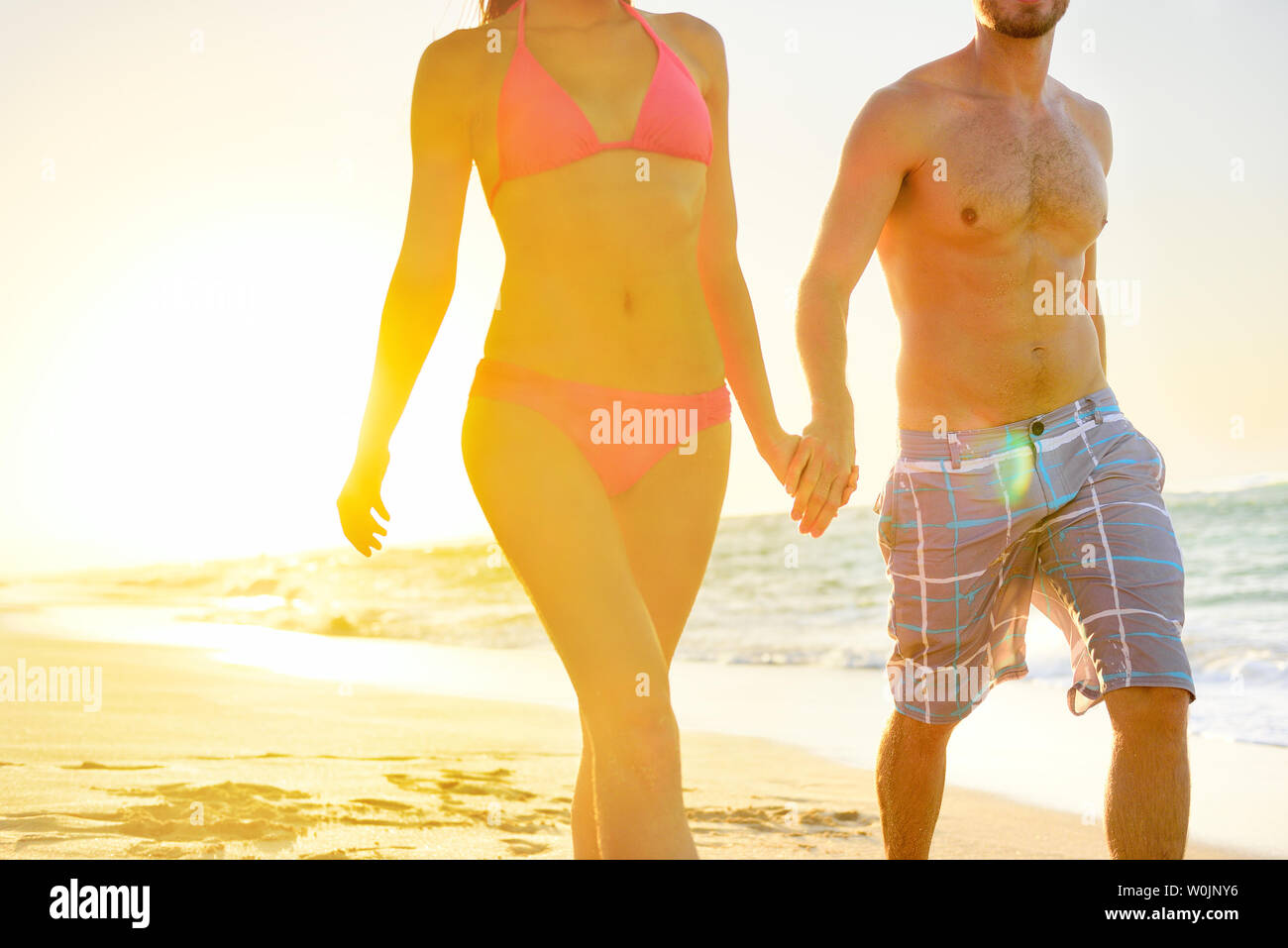 Summer beach couple romantic holding hands at sunset walking in love on honeymoon travel vacation holidays. Unrecognizable woman and man in happy romance wearing bikini and casual beachwear shorts. - Stock Image