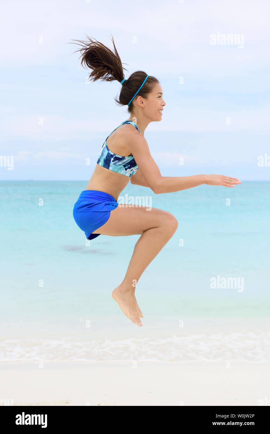 Crossfit fitness Asian woman on beach doing jump squat