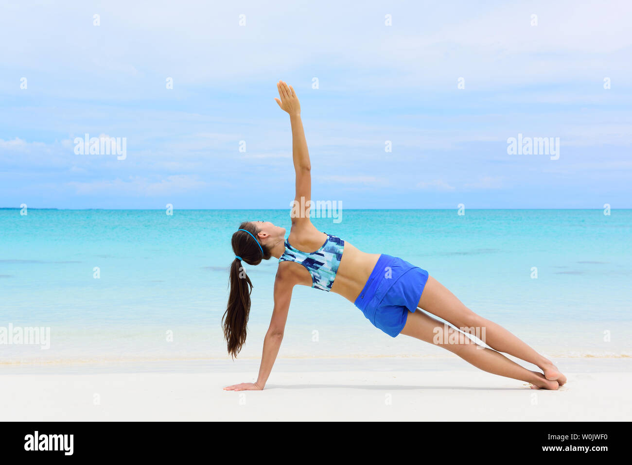 Fitness woman strength training her body core muscles with yoga pose. Athlete planking on one arm doing side plank and hip lift. - Stock Image