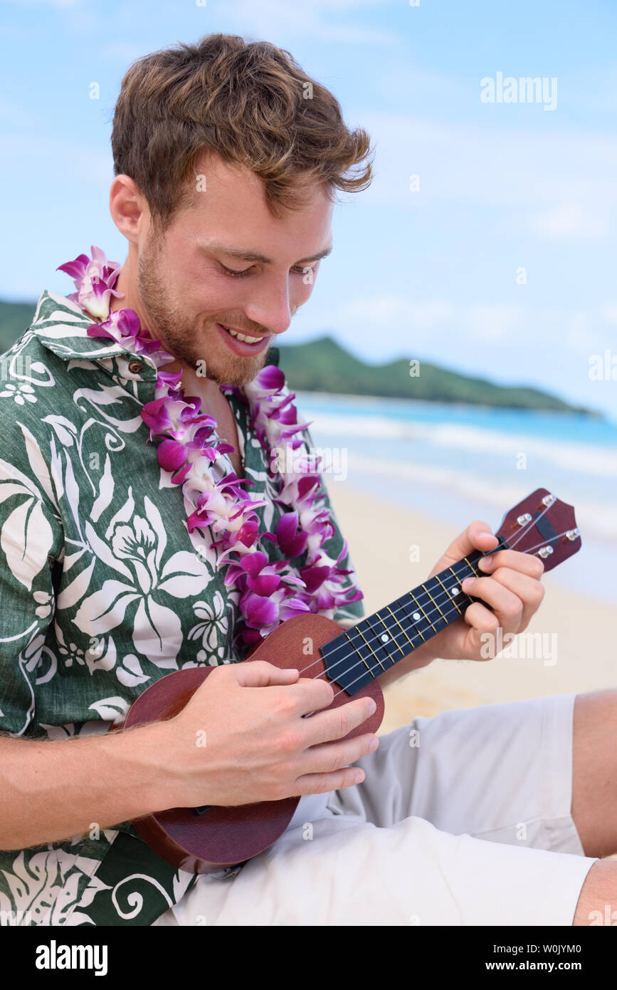 Man on beach playing ukulele instrument on Hawaii. Young man practicing on beach vacations in Hawaiian clothing wearing Aloha shirt dress and flower lei. - Stock Image