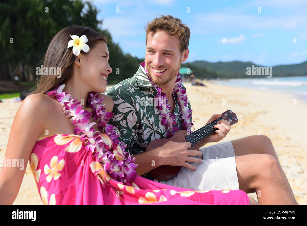 Man on beach playing ukulele instrument on Hawaii with having fun. Young couple, woman and man in love on beach vacations in Hawaiian clothing wearing Aloha shirt dress and flower lei. - Stock Image