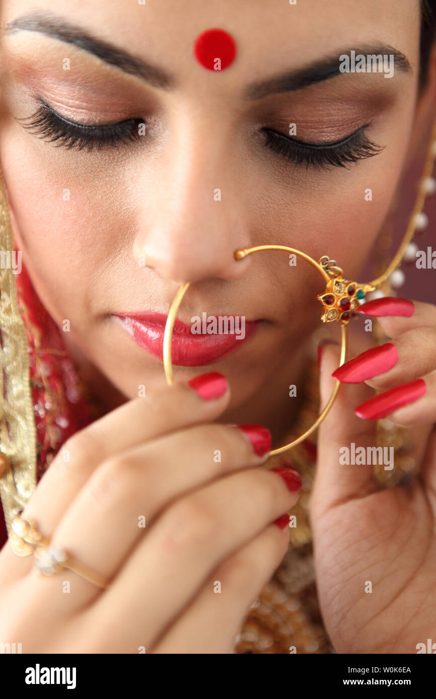 Close Up Of An Indian Bride Adjusting Her Nose Ring Stock Photo