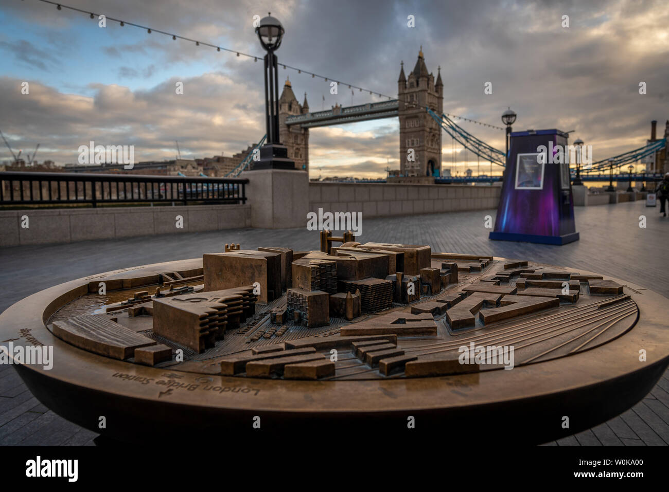 LONDON, ENGLAND, DECEMBER 10th, 2018: Tower Bridge in London, United Kingdom. Sunrise with beautiful clouds and model of nearby tourist area. English - Stock Image