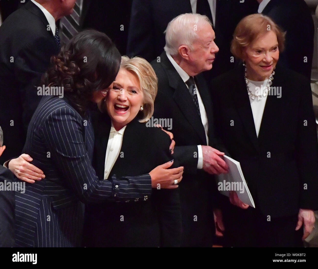 Hillary Clinton hugs Michelle Obama as former presidents and spouses assemble at the funeral of President George H.W. Bush at the National Cathedral in Washington D.C. on December 5, 2018. At right ,Jimmy Carter and his wife Rosalynn talk.      Photo by Kevin Dietsch/UPI Stock Photo