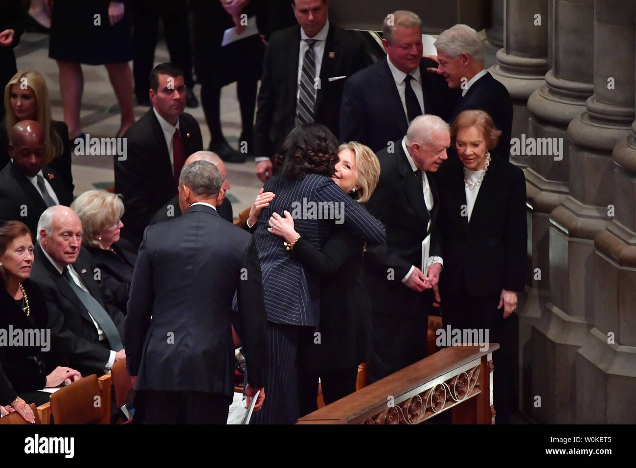 Hillary Clinton hugs Michelle Obama as former presidents and spouses assemble at the funeral of President George H.W. Bush at the National Cathedral in Washington D.C. on December 5, 2018. At right, Jimmy Carter and his wife Rosalynn talk in front of Bill Clinton chating with Al Gore.  Photo by Kevin Dietsch/UPI Stock Photo