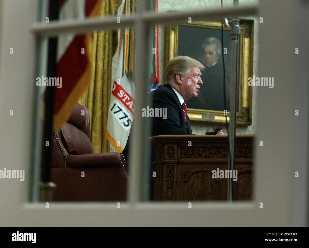 President Donald Trump deliver a televised address to the nation from the Oval Office at the White House in Washington, DC on January 8, 2019.  Photo taken through the Oval Office windows.   The speech comes on the 18th day of a partial government shutdown cause by a dispute over a proposed border wall separating the United States and Mexico.     Photo by Kevin Dietsch/UPI - Stock Image