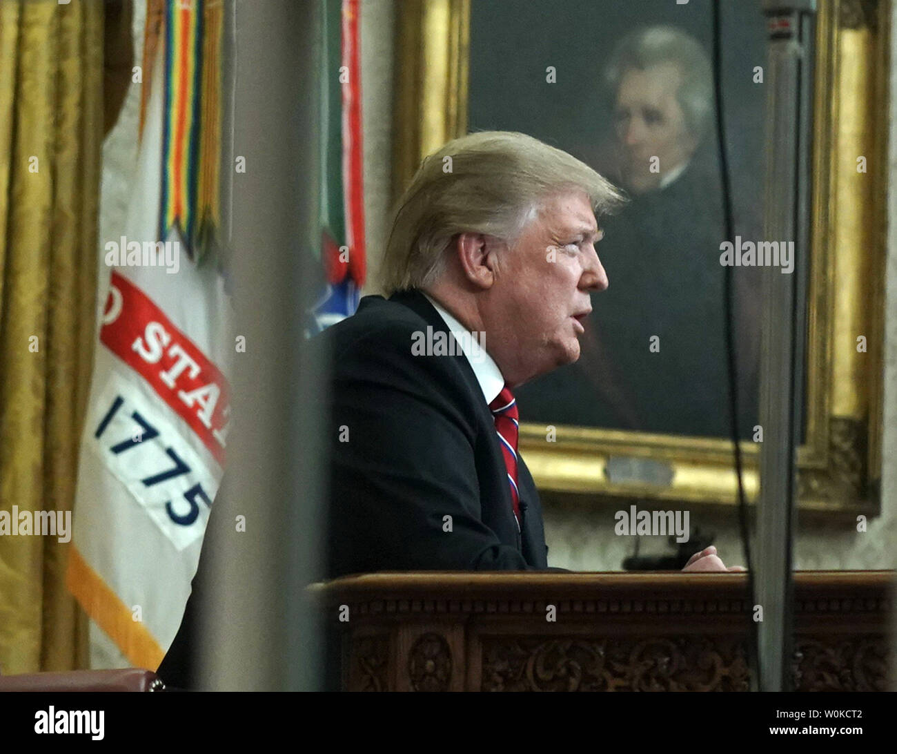 President Donald Trump delivers a televised address to the nation from the Oval Office at the White House in Washington, DC on January 8, 2019.  Photo taken through the Oval Office windows.   The speech comes on the 18th day of a partial government shutdown cause by a dispute over a proposed border wall separating the United States and Mexico.     Photo by Kevin Dietsch/UPI - Stock Image