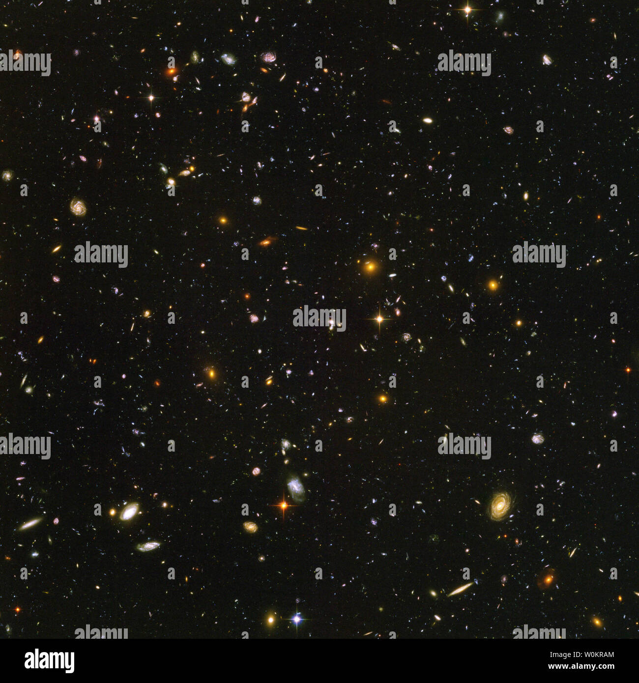 Galaxies, galaxies everywhere - as far as NASA's Hubble Space Telescope can see. This view of nearly 10,000 galaxies is the deepest visible-light image of the cosmos. Called the Hubble Ultra Deep Field, this galaxy-studded view represents a 'deep' core sample of the universe, cutting across billions of light-years. The snapshot includes galaxies of various ages, sizes, shapes, and colors. The smallest, reddest galaxies, about 100, may be among the most distant known, existing when the universe was just 800 million years old. The nearest galaxies - the larger, brighter, well-defined spirals and - Stock Image
