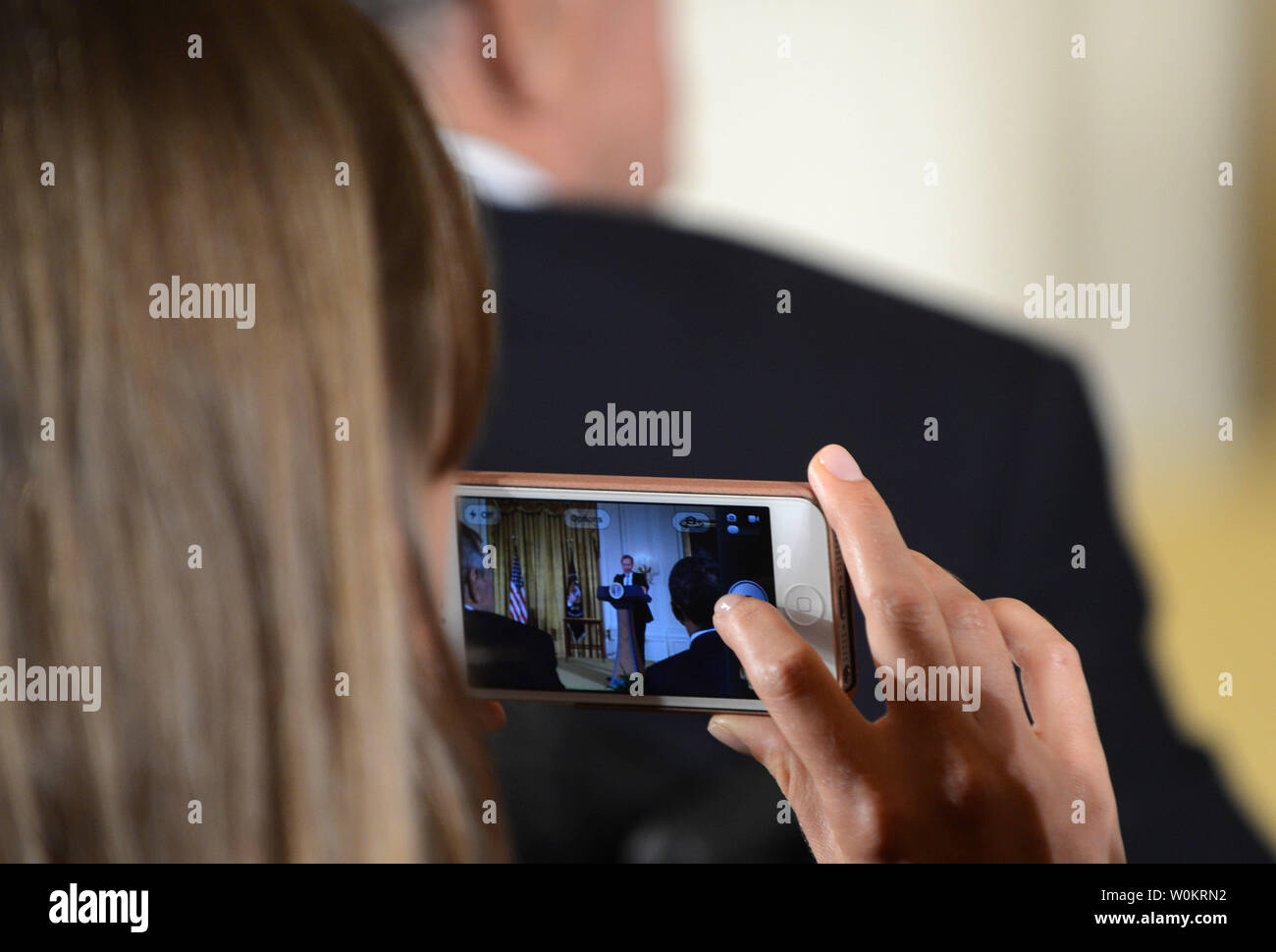 A member of the audience uses a smartphone to take a picture of former President George H.W. Bush (L) and President Barack Obama sitting in front of her during the presentation of the 5,000th 'Points of Light' Foundation award in the East Room of the White House in Washington, DC on July 15, 2013.  President Bush started the national movement to advance volunteerism and community service 20 years ago when he was the 41st president.  Kathy Hamilton and Floyd Hammer won the award.   UPI/Pat Benic - Stock Image
