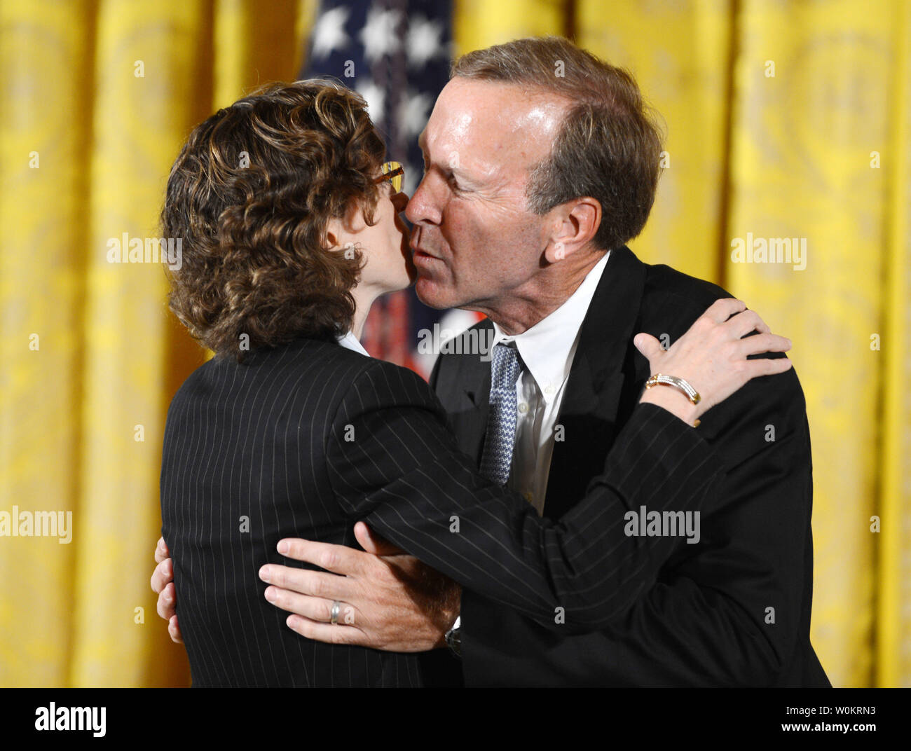 Points of Light Foundation Chairman Neil Bush, son of former President George H.W. Bush, hugs Points of Light Foundation CEO Michelle Nunn during the presentation of the 5,000th 'Points of Light' Foundation award with President Barack Obama in the East Room of the White House in Washington, DC on July 15, 2013.  President Bush started the national movement to advance volunteerism and community service 20 years ago when he was the 41st president.  Kathy Hamilton and Floyd Hammer won the award.   UPI/Pat Benic - Stock Image