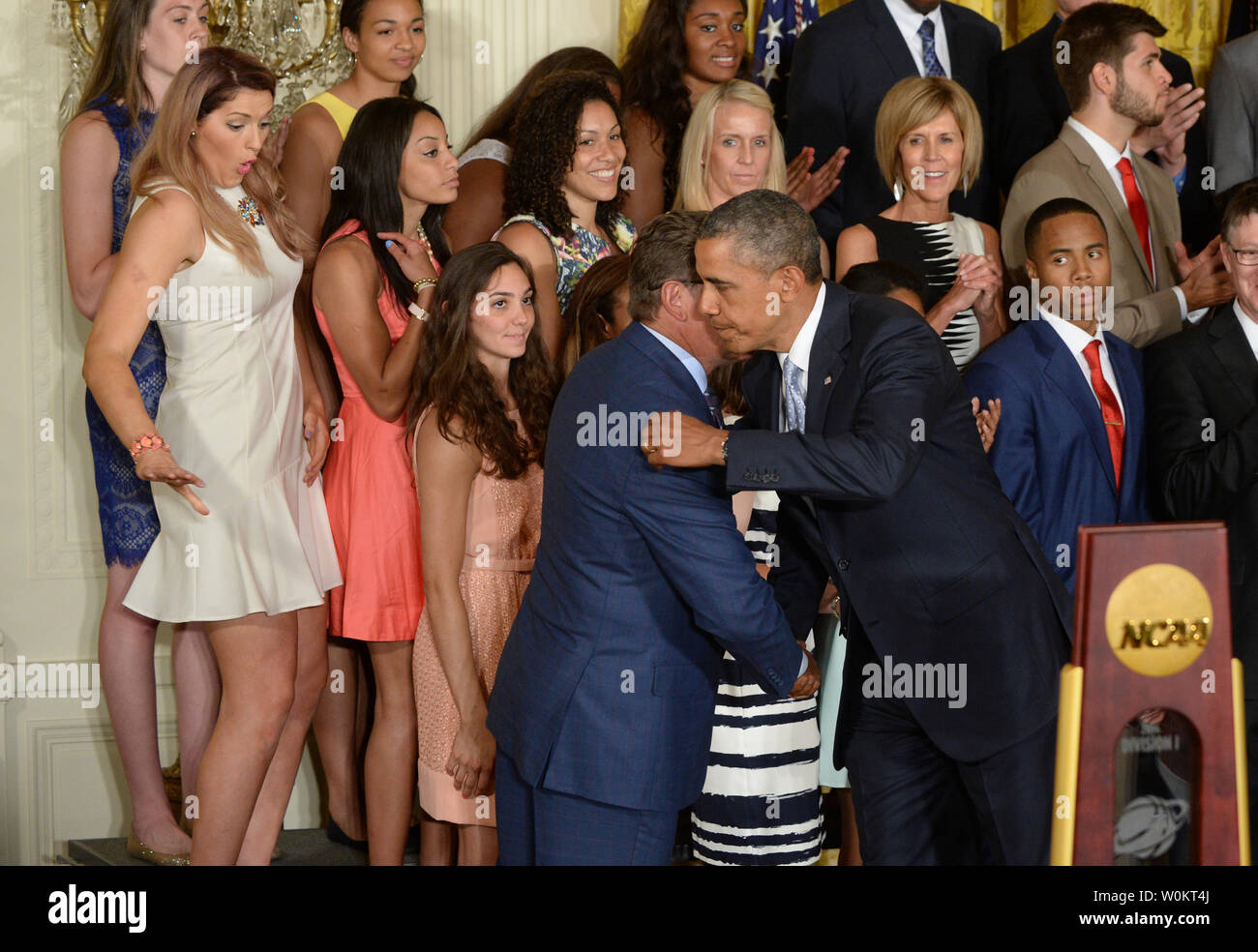 University of Connecticut star basketball player Stefanie Dolson (L) slips off the podium riser as U.S. President Barack Obama hugs head coach Geno Auriemma during a presentation in the East Room of the White House in Washington, DC on June 9, 2014.  Obama honored both the women's and men's basketball teams from the University of Connecticut as they both won the NCAA collegiate basketball championships for the 2013-2014 season.    UPI/Pat Benic - Stock Image