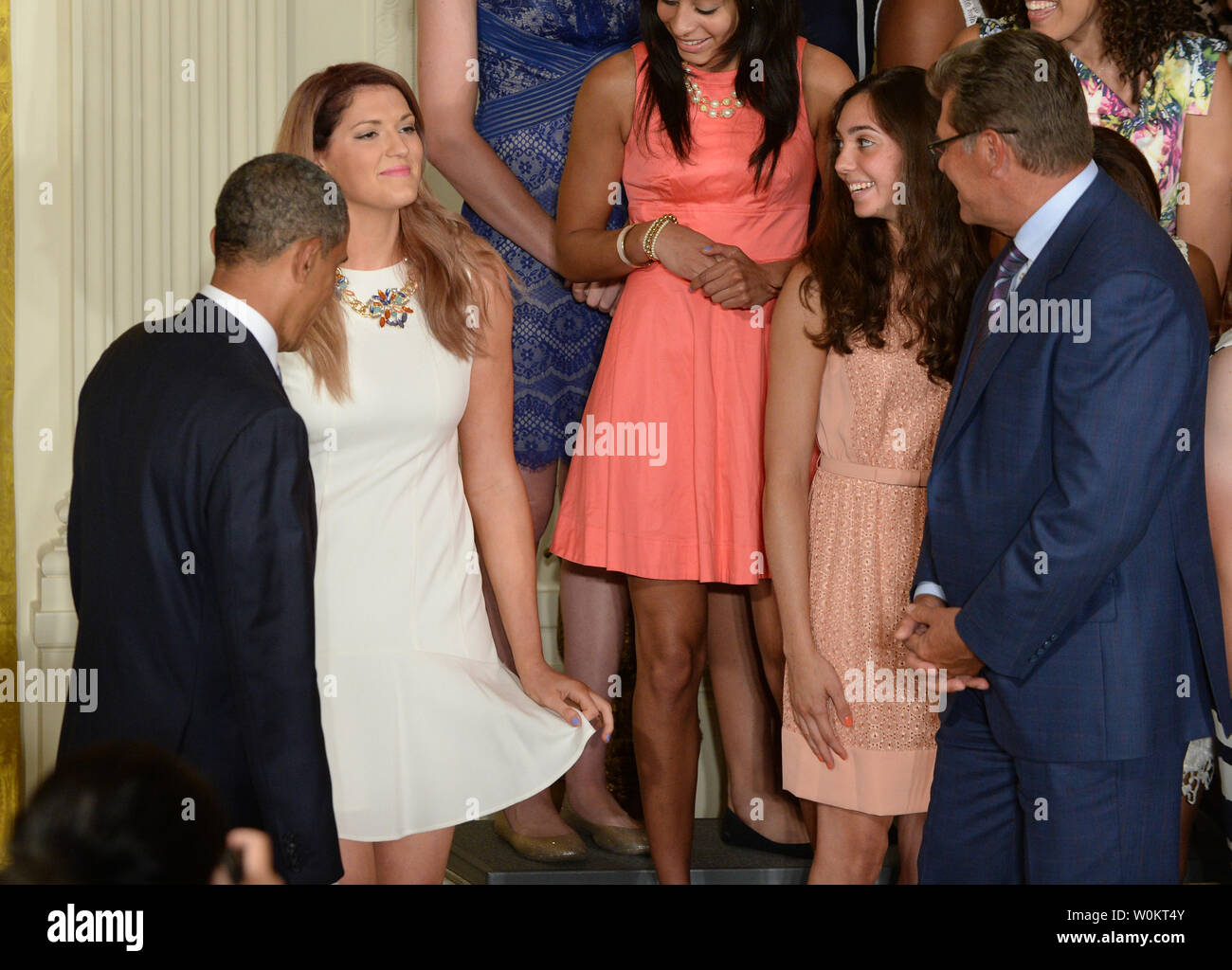 University of Connecticut star basketball player Stefanie Dolson curtsies after she slipped off the podium riser while President Barack Obama (L) was shaking hands with head coach Geno Auriemma (R) during a presentation in the East Room of the White House in Washington, DC on June 9, 2014.  Obama honored both the women's and men's basketball teams from the University of Connecticut as they both won the NCAA collegiate basketball championships for the 2013-2014 season.    UPI/Pat Benic - Stock Image