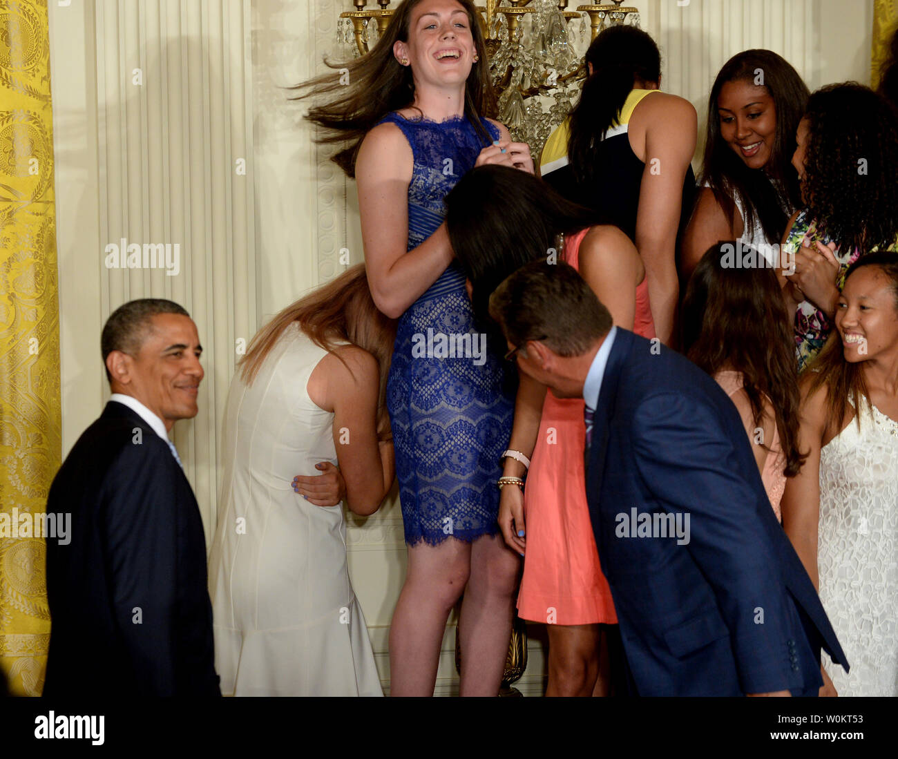 U.S. President Barack Obama smiles as he see that University of Connecticut star basketball player Stefanie Dolson (white dress) is all right but embarrassed after she slipped off the podium riser while Obama was shaking hands with head coach Geno Auriemma (R) during a presentation in the East Room of the White House in Washington, DC on June 9, 2014.  Obama honored both the women's and men's basketball teams from the University of Connecticut as they both won the NCAA collegiate basketball championships for the 2013-2014 season.    UPI/Pat Benic - Stock Image