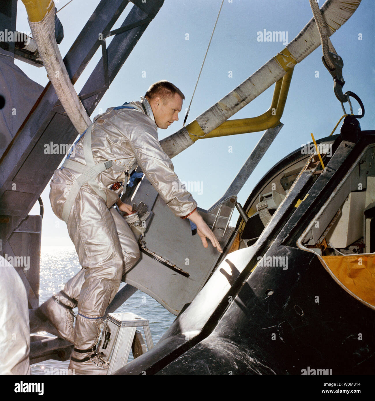 NASA astronaut Neil Armstrong, prime crew Command pilot on Gemini 8, climbs into a full-scale model of the Gemini spacecraft during water egress training on the Gulf of Mexico in January 15, 1966. March 16, 2016 marks the 50th anniversary of NASA's Gemini 8 mission, the sixth manned spaceflight conducted during the United States' Project Gemini program. The primary objective of the mission, the successful docking of two spacecraft in orbit, a first in spaceflight, was a success though the crew would experience a critical in-space system failure, forcing them to abandon the mission prematurely. Stock Photo