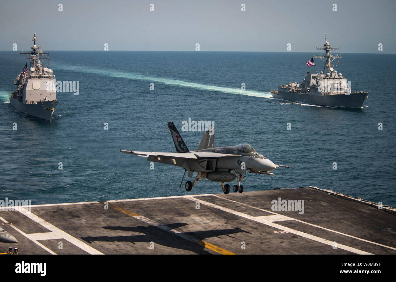 """An F/A-18E Super Hornet from the """"Kestrels"""" of Strike Fighter Squadron (VFA) 137 lands on May 3, 2017, on the flight deck of the Nimitz-class aircraft carrier USS Carl Vinson (CVN 70) as the Ticonderoga-class guided-missile cruiser USS Lake Champlain (CG 57), left, and the Arleigh Burke-class guided-missile destroyer USS Wayne E. Meyer (DDG 108) transit the western Pacific Ocean. The U.S. Navy has patrolled the Indo-Asia-Pacific routinely for more than 70 years promoting regional peace and security.  Photo by MC2 Z.A. Landers/U.S. Navy/UPI Stock Photo"""