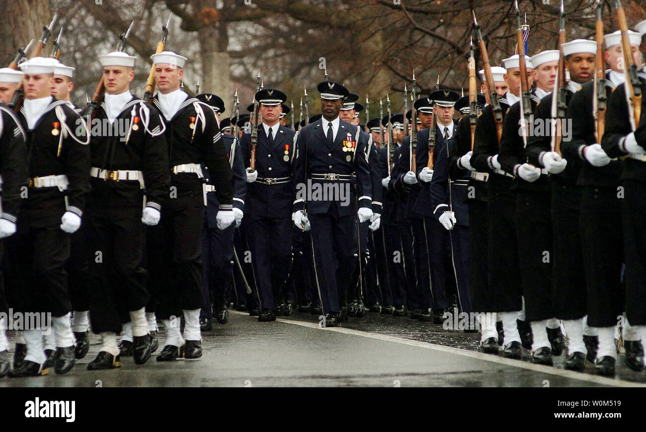 Members of the U.S. Forces Honor Guard march during the funeral for retired Adm. Thomas H. Moorer on February 20, 2004, at Arlington National Cemetary. Adm. Moorer is a graduate of the Naval Academy class of1933 and went on to serve as the Chief of Naval Operations from 1967-1970, whereupon he was appointed Chairman of the Joint Chiefs of Staff, a post he held until his retirement in 1974. A former naval aviator, Moorer earned many personal decorations and honors during his career, including the Department of Defense Distinguished Service Medal and the Distinguished Flying Cross.   (UPI Photo/ - Stock Image