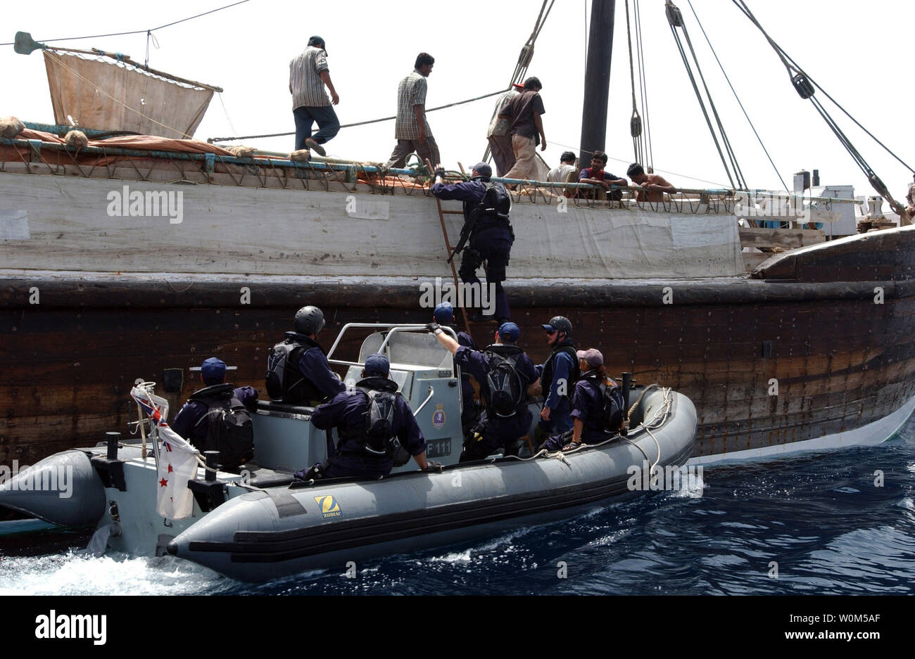 Boarding Team Members from New Zealand's HMNZS Te Mana (F 111) embark a local transport dhow, from a Rigid Hull Inflatable Boat (RHIB) while conducting a search of the vessel in the Gulf of Oman on May 2, 2004.   (UPI Photo/Bart Bauer/US Navy) - Stock Image