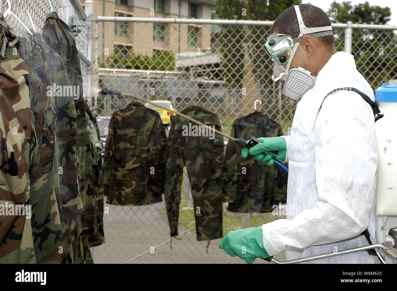 In preparation of deployment to Indonesia with the Naval Environmental Preventive Medicine Unit, Ron Berard sprays uniforms with Permethrin mosquito repellant on December 30, 2004 in Pearl Harbor, Hawaii. The unites will assist humanitarian relief efforts by providing water quality testing, bug spraying, and medical care for Tsunami survivors.      (UPI Photo/Jennifer L. Bailey  via Navy) - Stock Image