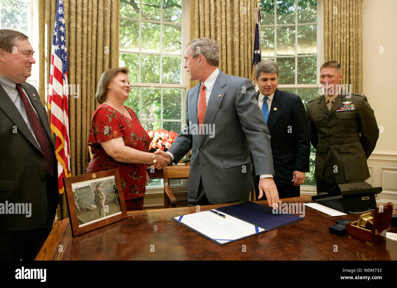 President George W. Bush shakes the hand of Janet Norwood after signing into law H.R. 1001, the Naming of the Sergeant Byron W. Borwood Post Office Building, designating the US Postal Service facility in Pflugerville, Texas, in honor of the 25-year-old Marine who died in combat, in the White House on July 21, 2001.  Joining Mrs. Norwood and the President for the signing are, from left:  Bill Norwood, husband and father; Congressman Michael McCaul, R-Texas, and First Lt. T. Ryan Sparks, 3rd Battalion, 1st Marines.    (UPI Photo/Eric Draper/White House) Stock Photo