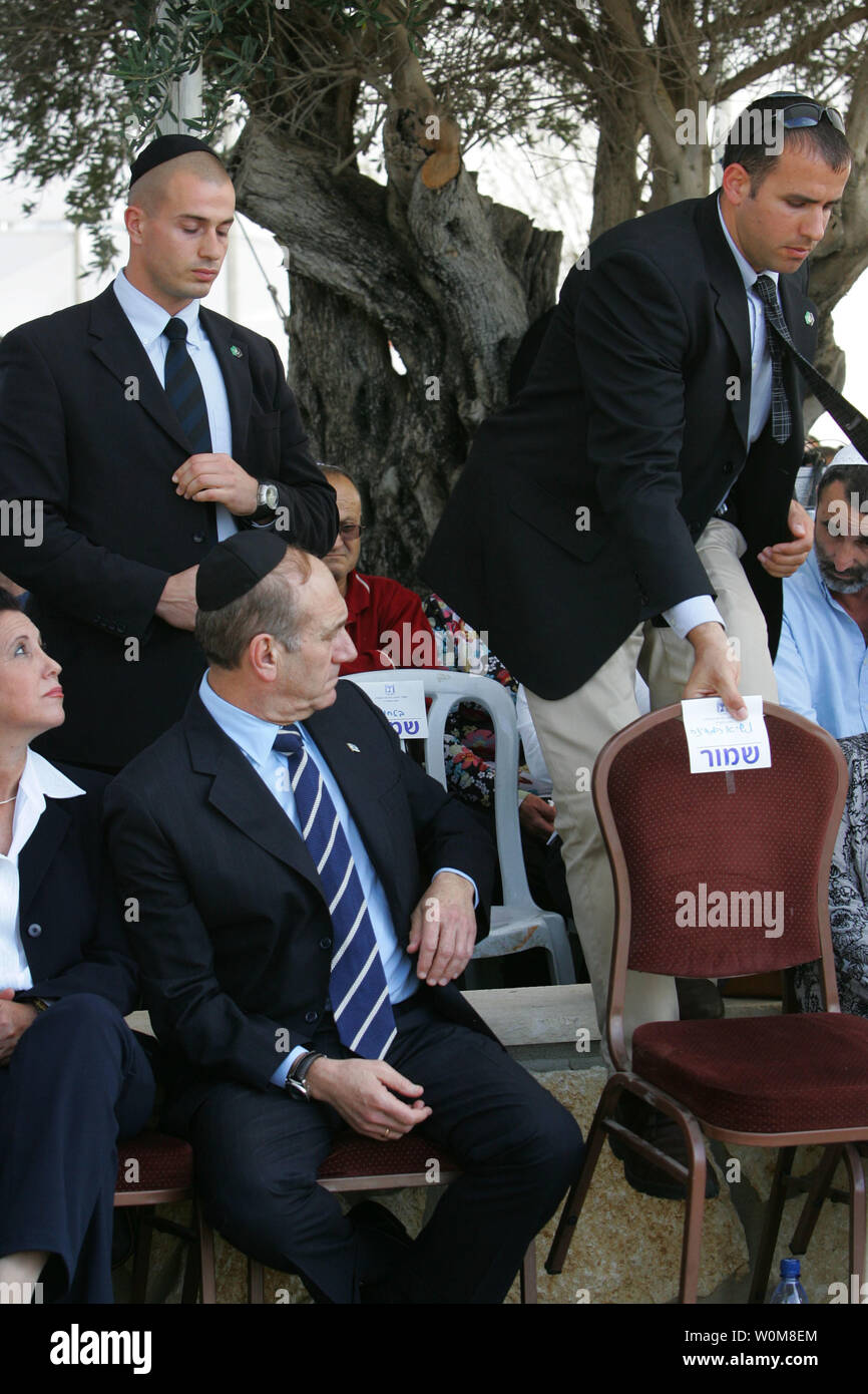 Israeli Acting Prime Minister Ehud Olmert watches as a secret service bodyguard climbs over chairs to follow Israeli President Moshe Katsav, unseen, to the podium during a memorial service for the late Israeli President Ezer Weizman on the first anniversary of his death April 10, 2006 at his graveside in the northern Israeli town of Or Akiva.    (UPI Photo/David Silverman/POOL) - Stock Image