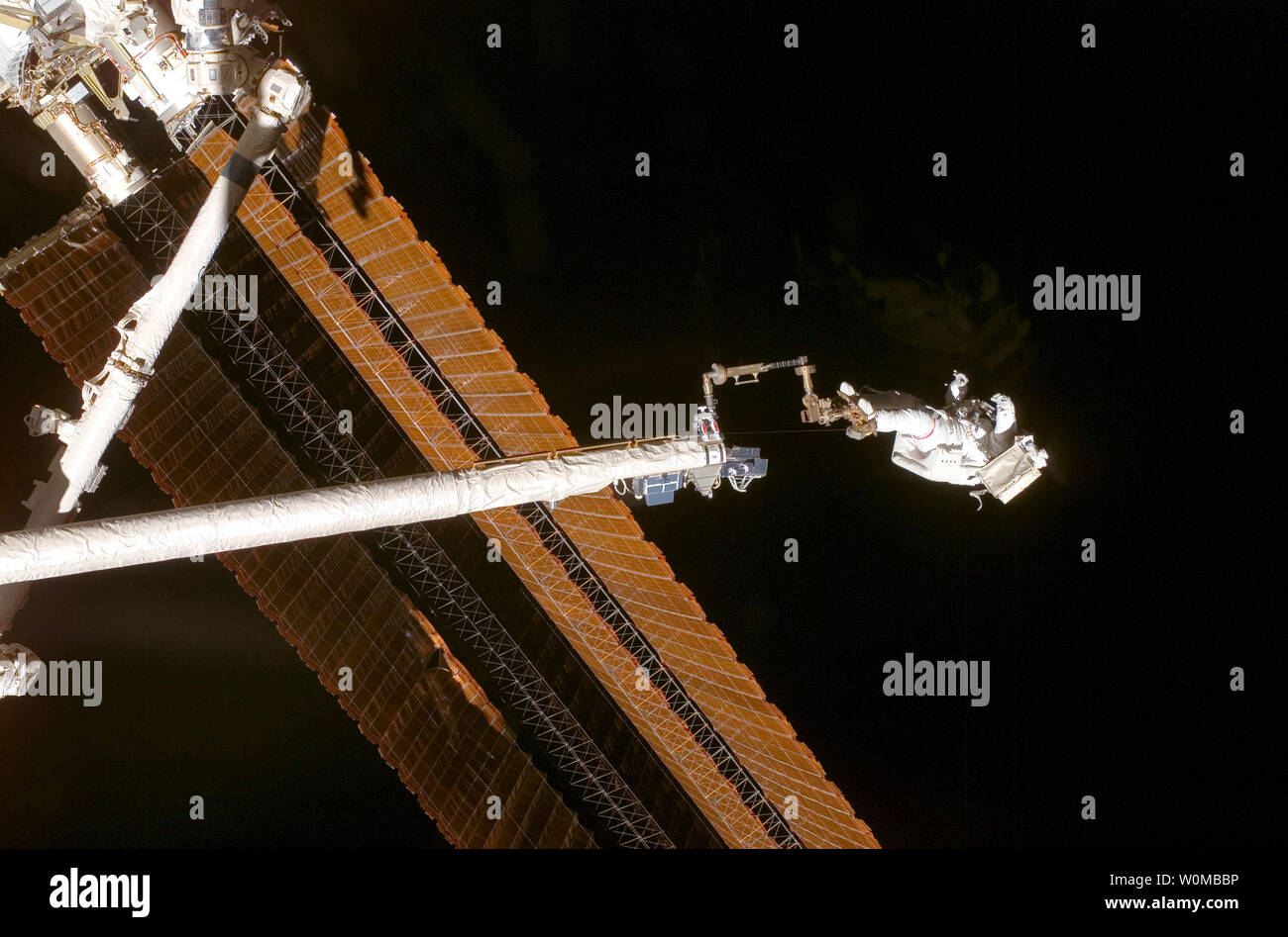 While anchored to a foot restraint on the end of the Orbiter Boom Sensor System (OBSS), astronaut Scott Parazynski, STS-120 mission specialist, assesses his repair work as the solar array is fully deployed during the mission's fourth session of extravehicular activity (EVA) while Space Shuttle Discovery is docked with the International Space Station on November 3, 2007. During the 7-hour, 19-minute spacewalk, Parazynski cut a snagged wire and installed homemade stabilizers designed to strengthen the damaged solar array's structure and stability in the vicinity of the damage. Astronaut Doug Whe - Stock Image