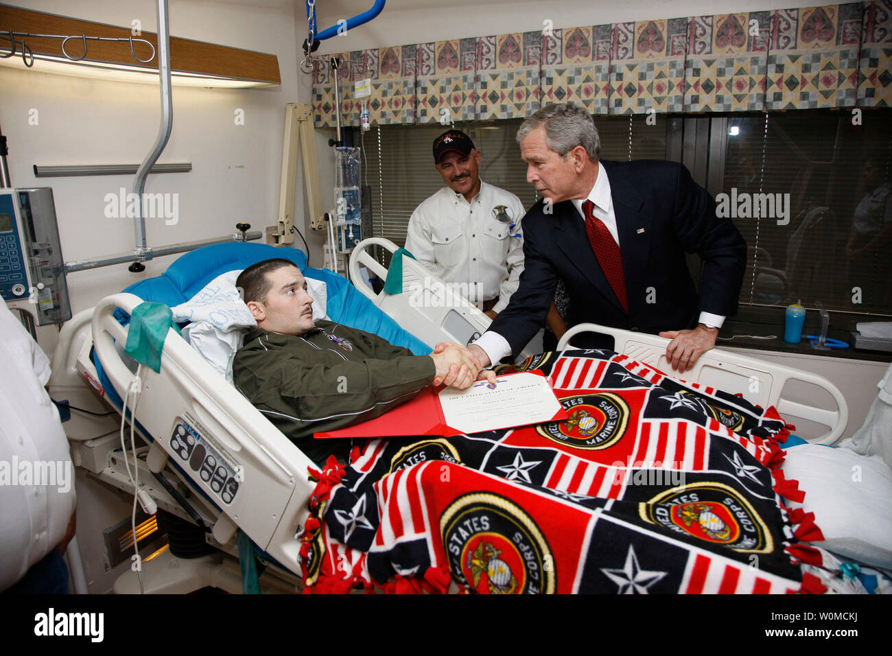 U.S. President George W. Bush shakes hands with U.S. Marine Corps Lance Cpl. Justin Rokohl of Orange Grove, Texas, after awarding him a Purple Heart medal at the Walter Reed National Military Medical Center in Bethesda, Maryland on July 3, 2008. Rokohl's father, John, looks on. (UPI Photo/Eric Draper/White House Press Office) Stock Photo