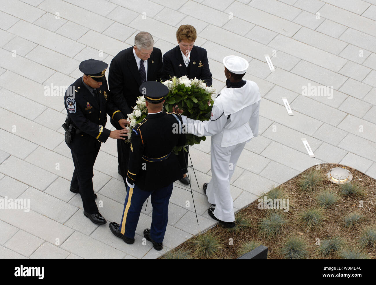 Former chairman of the Joint Chiefs of Staff Retired U.S. Air Force Gen. Richard B. Myers (2nd L), American Airlines flight attendant Deborah Maitland-Rowland (2nd R) and Lt. David Webster, a Pentagon Force Protection Agency officer (L) place a wreath during the dedication ceremony for the Pentagon Memorial on the seventh anniversary of the September 11, 2001 terrorist attacks on the Pentagon and the World Trade Center in New York City, at the Pentagon in Arlington, Virginia on September 11, 2008. (UPI Photo/Jennifer Villalovos/U.S. Navy) - Stock Image