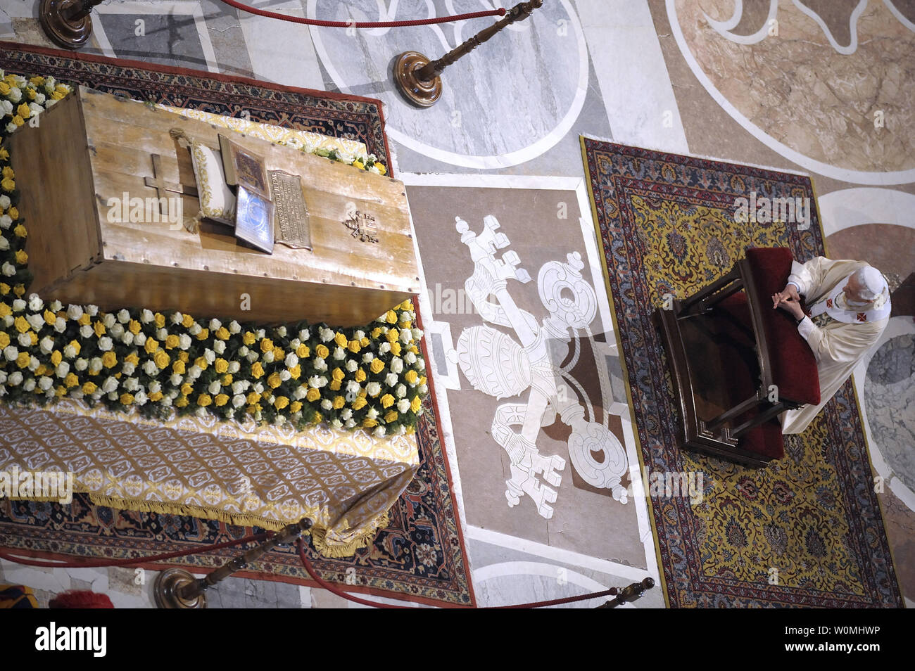Pope Benedict XVI kneels before the coffin of his predecessor Pope John Paul II in St. Peter's Basilica in the Vatican following his beatification on May 1, 2011.   UPI/Stefano Spaziani Stock Photo