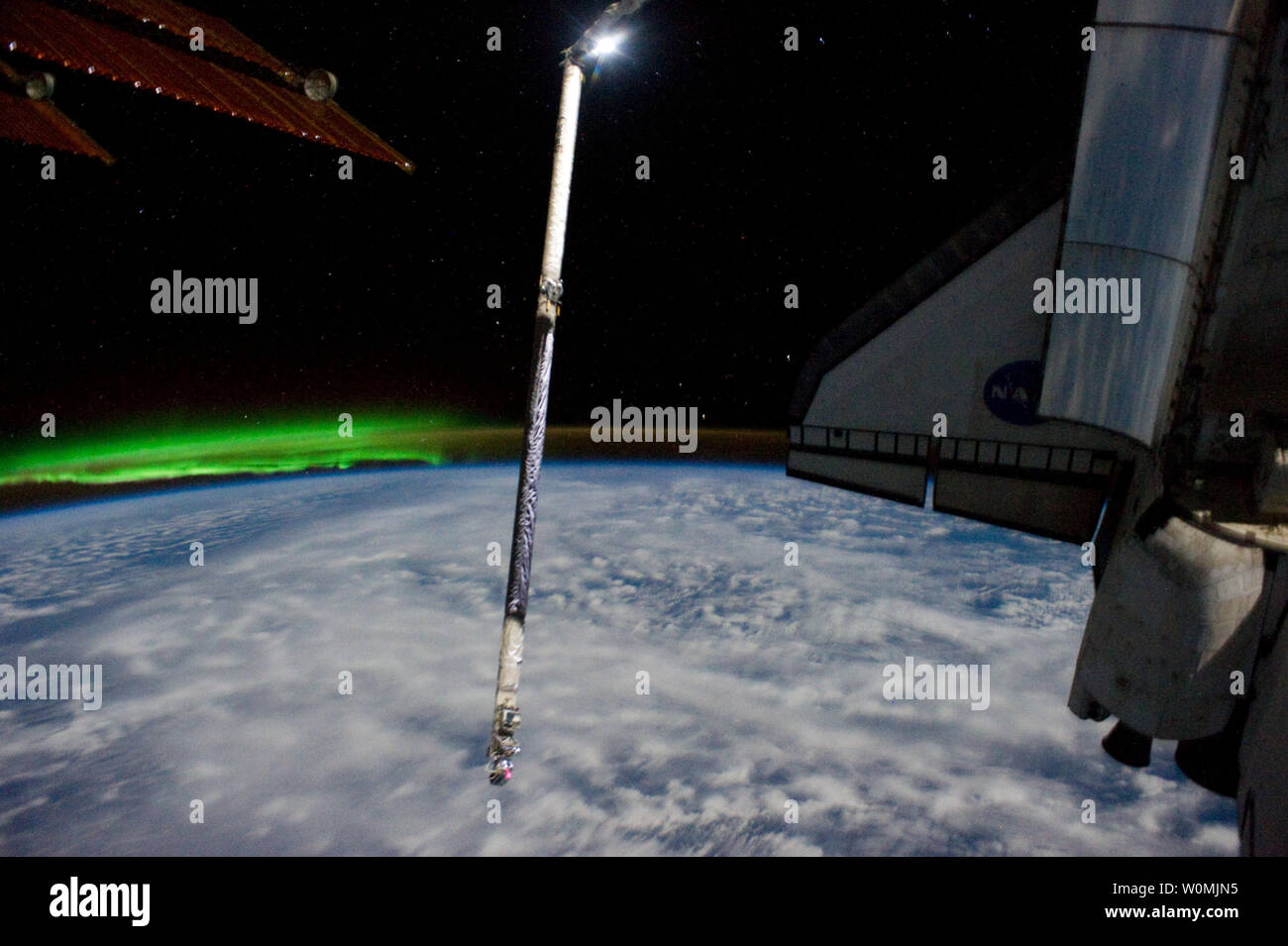 This NASA image taken on July 14, 2011 by a members of the joint crews of NASA mission STS-135 and crew onboard the International Space Station shows this image of Atlantis and its Orbital Boom Sensor System robot arm extension backdropped against Earth's horizon and a greenish phenomenon associated with Aurora Australis. One of the station's solar array panels appears at upper left. Space Shuttle Atlantis is at the International Space Station on mission STS-135, the final shuttle mission.  UPI/NASA - Stock Image