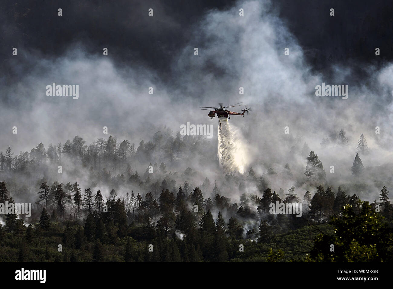 A helicopter drops water on the fire as firefighters continued to battle the blaze that burned into the evening hours in Waldo Canyon on the U.S. Air Force Academy, June 27, 2012. The fires, which have burned more than 15,000 acres, began spreading to the southwestern corner of the Academy in the early morning, causing base officials to evacuate residents. Officials estimated that the fire had spread to about 10 acres of land belonging to the Academy. Currently, more than 90 firefighters from the Academy, along with assets from Air Force Space Command; F.E. Warren Air Force Base, Wyoming; Fort Stock Photo