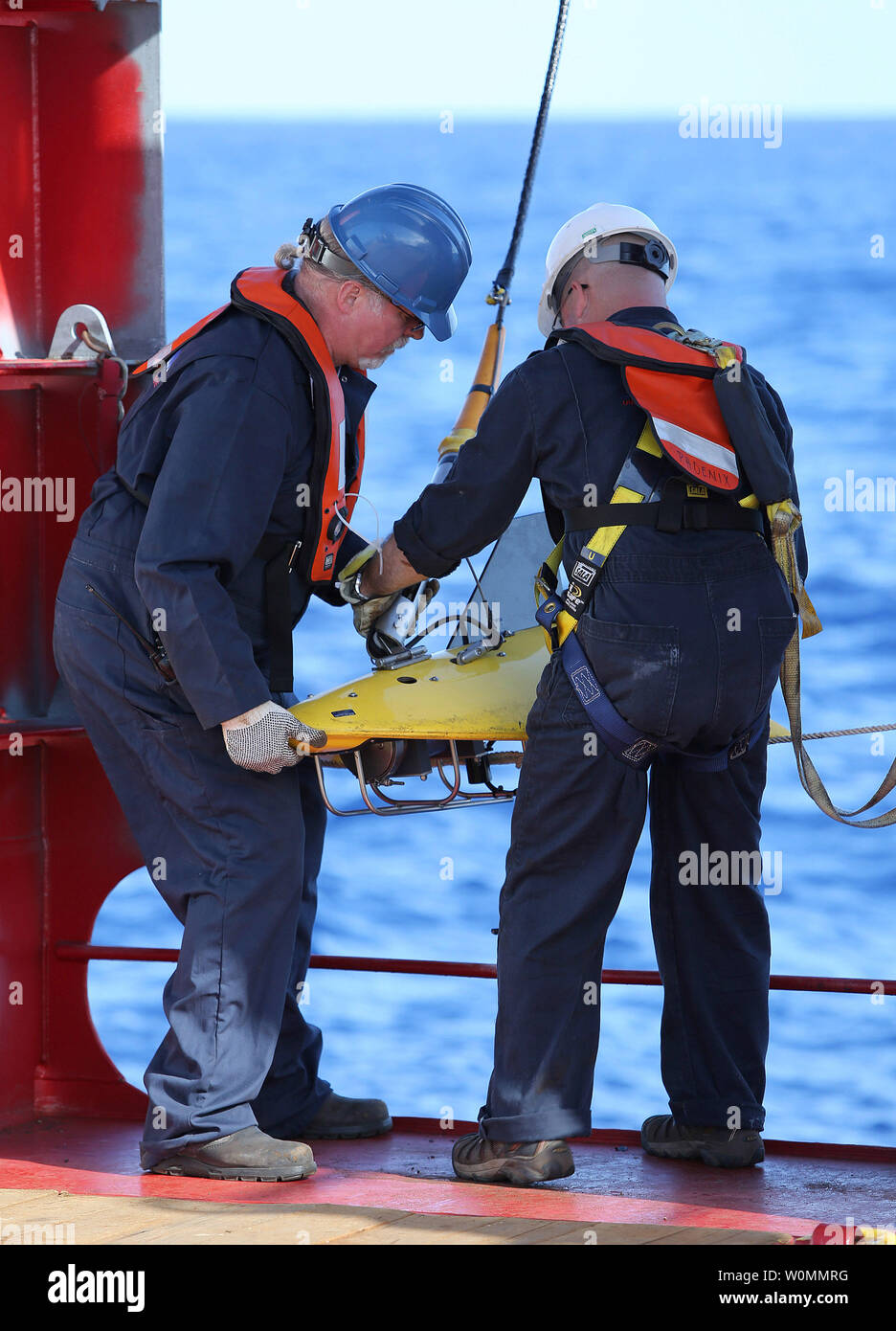 Phoenix International personnel deploy a 'towed pinger locator' off the deck of Australian Defense Vessel Ocean Shield in the search for the flight data recorder and cockpit voice recorder of a Malaysia Airlines jetliner missing in the Indian Ocean, about 1,000 miles off the coast of Perth, Australia.  The U.S. Navy 'towed pinger locator' connected to the Ocean Shield picked up signals consistent with that of the missing jetliner it was announced today April 7, 2014.   UPI/Kelly Hunt/Australian Defense Force - Stock Image