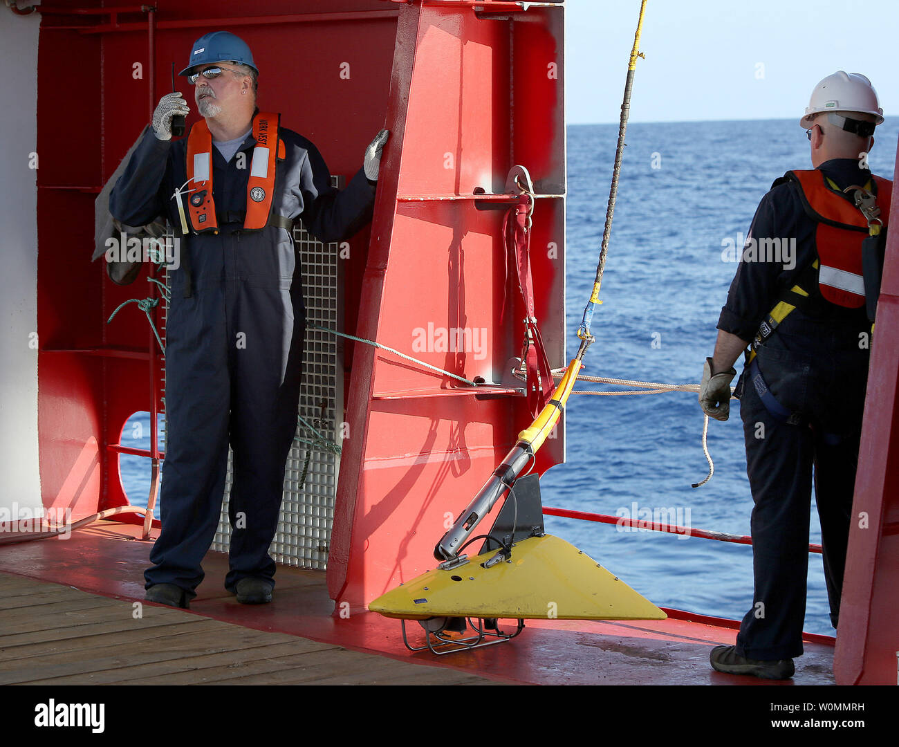 Phoenix International personnel prepare to deploy a 'towed pinger locator' off the deck of Australian Defense Vessel Ocean Shield in the search for the flight data recorder and cockpit voice recorder of a Malaysia Airlines jetliner missing in the Indian Ocean, about 1,000 miles off the coast of Perth, Australia.  The U.S. Navy 'towed pinger locator' connected to the Ocean Shield picked up signals consistent with that of the missing jetliner it was announced today April 7, 2014.   UPI/Kelly Hunt/Australian Defense Force - Stock Image