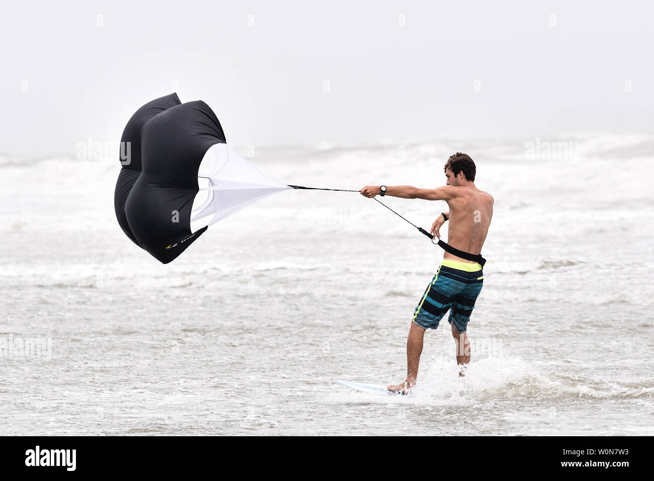 A young man uses a raining parachute to pull his boogie board along the incoming tide as winds reach 50-mph along the coast from Tropical Storm Hermine in Isle of Palms, South Carolina, on September 2, 2016.  Beach goers were discouraged from entering the water due to rip currents, turbulent waves and winds exceeding 50-mph.        Photo by Richard Ellis/UPI Stock Photo