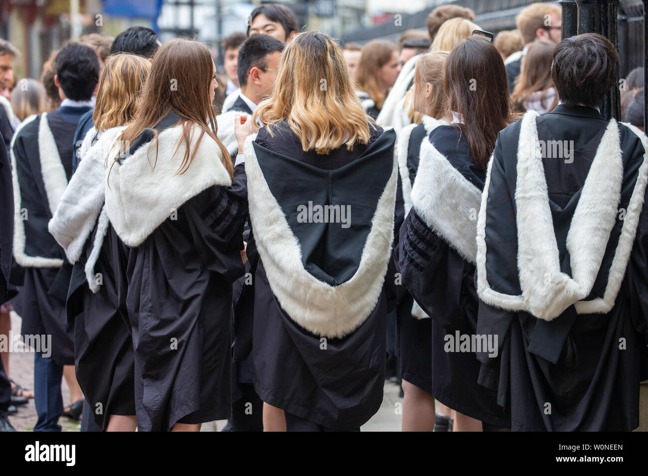 Cambridge University students from St John's College on the first day of this years graduation ceremonies at the Senate House.  Students dressed in black gowns as the traditional Cambridge University graduation ceremonies took place today (Wed).  The students paraded into historic Senate House watched by family and friends to collect their degrees from the prestigious university.  Many parts of the degree ceremonies, which will also be held over the next few days, have their origin amongst the earliest customs of the university 800 years ago.  Undergraduates are required to wear the gown of th - Stock Image