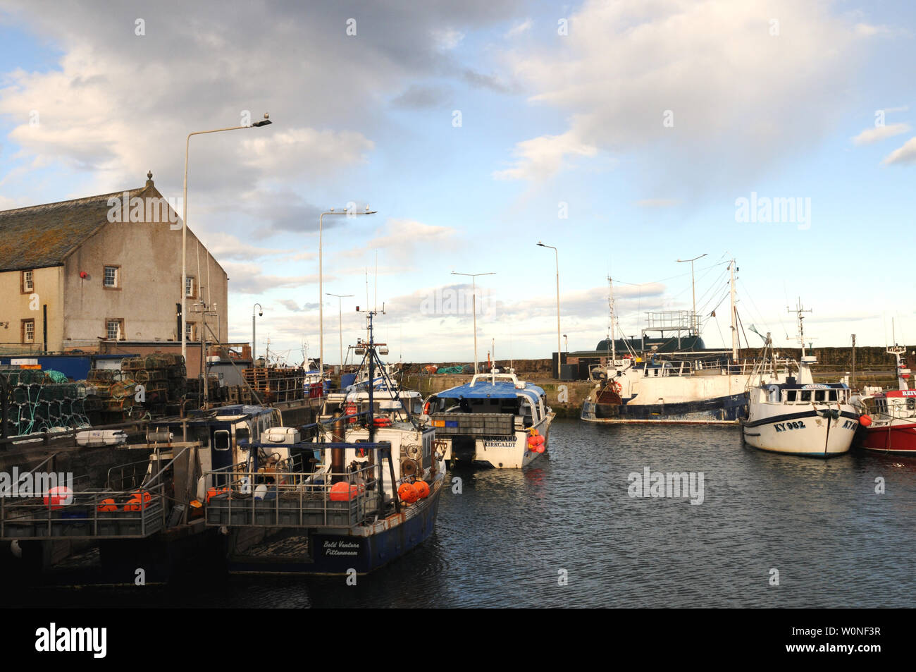 Fishing boats in harbour at Pittenweem a port on the Fife coast of Scotland. Fish is both landed and sold in the wholesale fish market in the port. - Stock Image