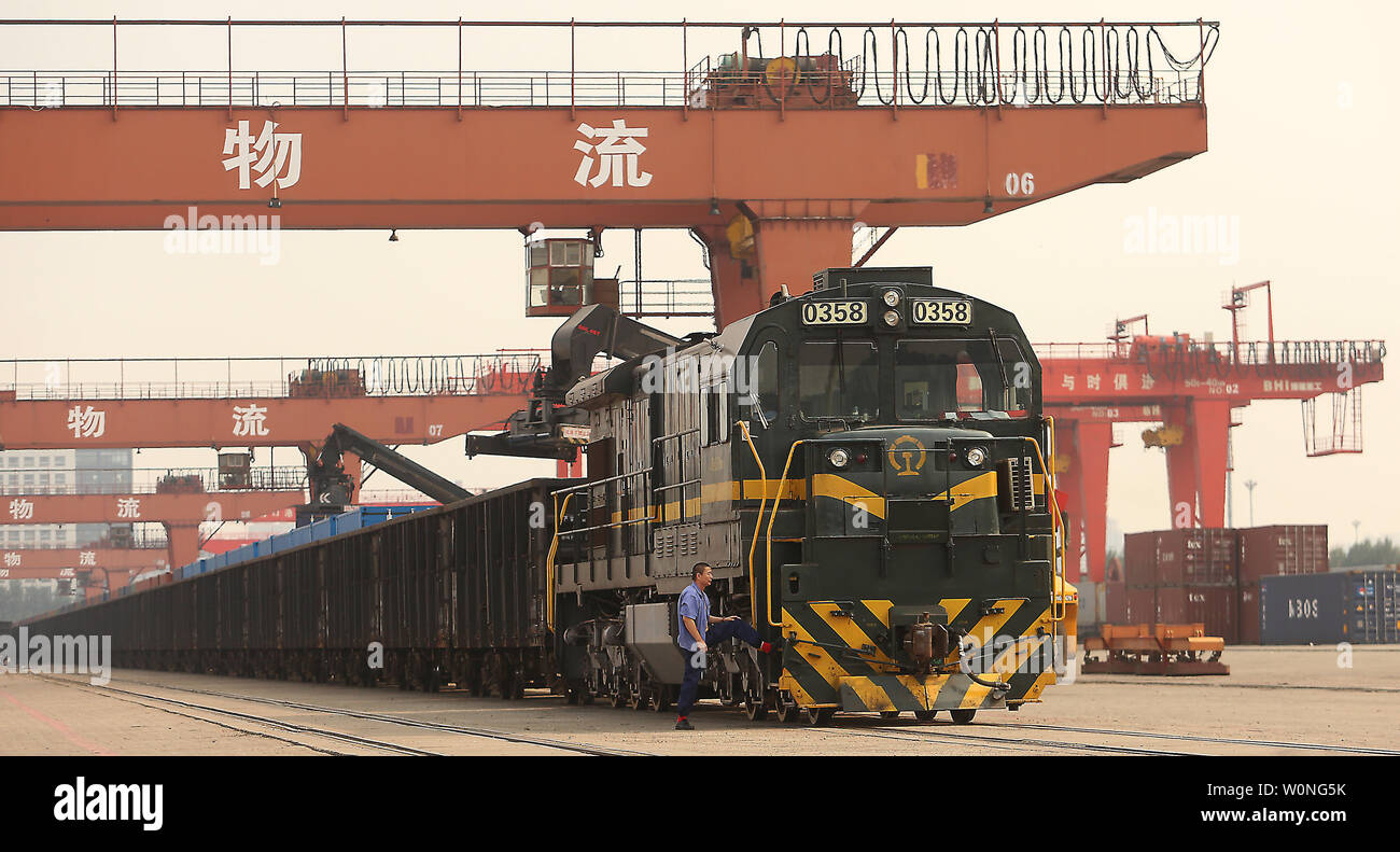 A Chinese train engineer stretches before transporting cargo containers from a port in Yingkou, a major port city in Liaoning Province, on July 18, 2018.  China's Ministry of Commerce is pursuing a legal remedy with the World Trade Organization (WTO) against the U.S. over new tariffs on $200 billion worth of Chinese exports.     Photo by Stephen Shaver/UPI - Stock Image
