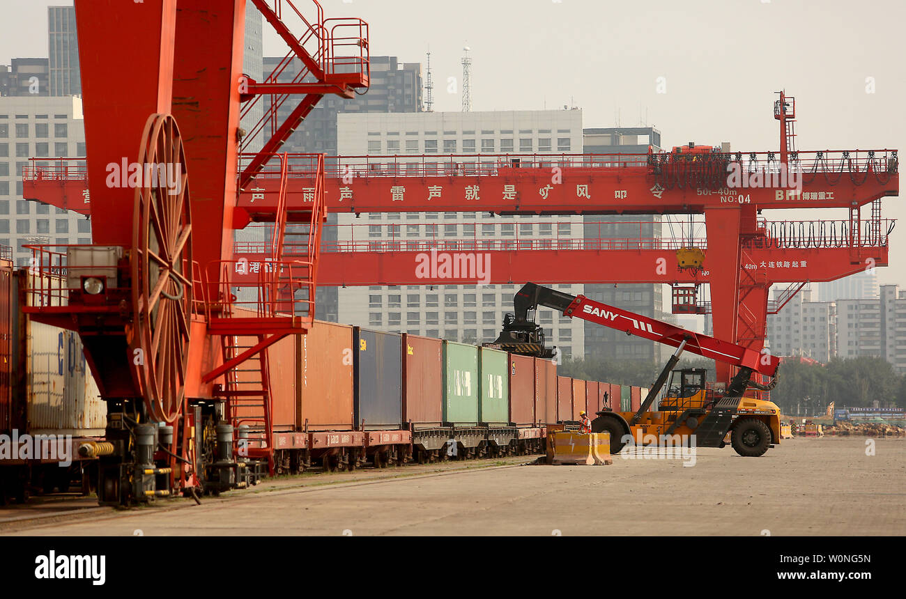 A Chinese crane unloads containers from a train onto trucks at a port in Yingkou, a major port city in Liaoning Province, on July 18, 2018.  China's Ministry of Commerce is pursuing a legal remedy with the World Trade Organization (WTO) against the U.S. over new tariffs on $200 billion worth of Chinese exports.     Photo by Stephen Shaver/UPI - Stock Image