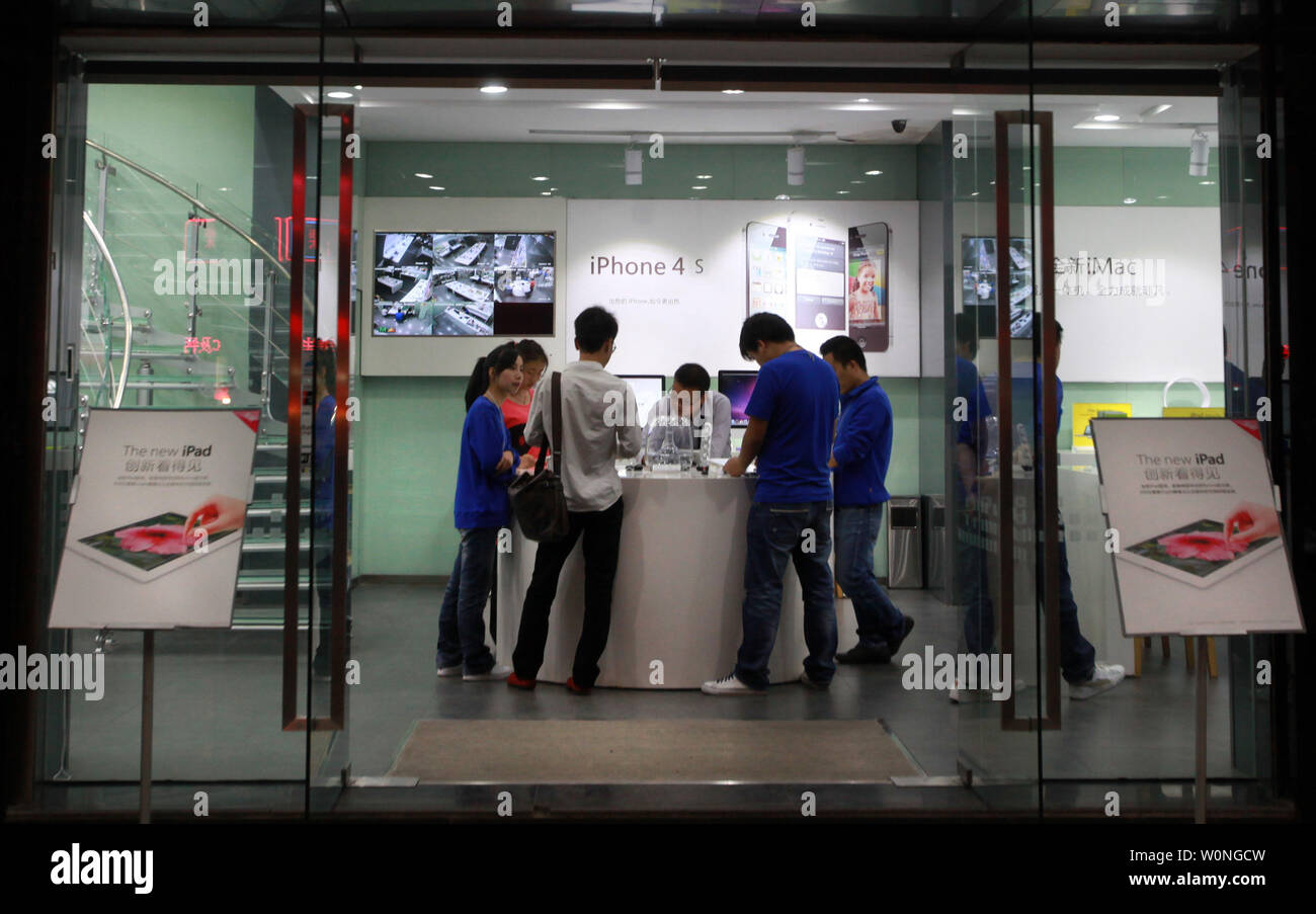 """Chinese employees dressed as official Apple staff work at a computer store flagrantly touting itself as an official """"Apple Smart Store,"""" selling customers real and 'gray' Apple products in Kunming, the capital of Yunnan Province, on September 24, 2012.  Kunming has had several """"Apple"""" stores cease and desist last year do to openly disregarding copyright and trademark infringements.  As the case stands, many times a show of force by the government to attack and solve such problems is usually only temporary in order to appease the claimants.   UPI/Stephen Shaver Stock Photo"""
