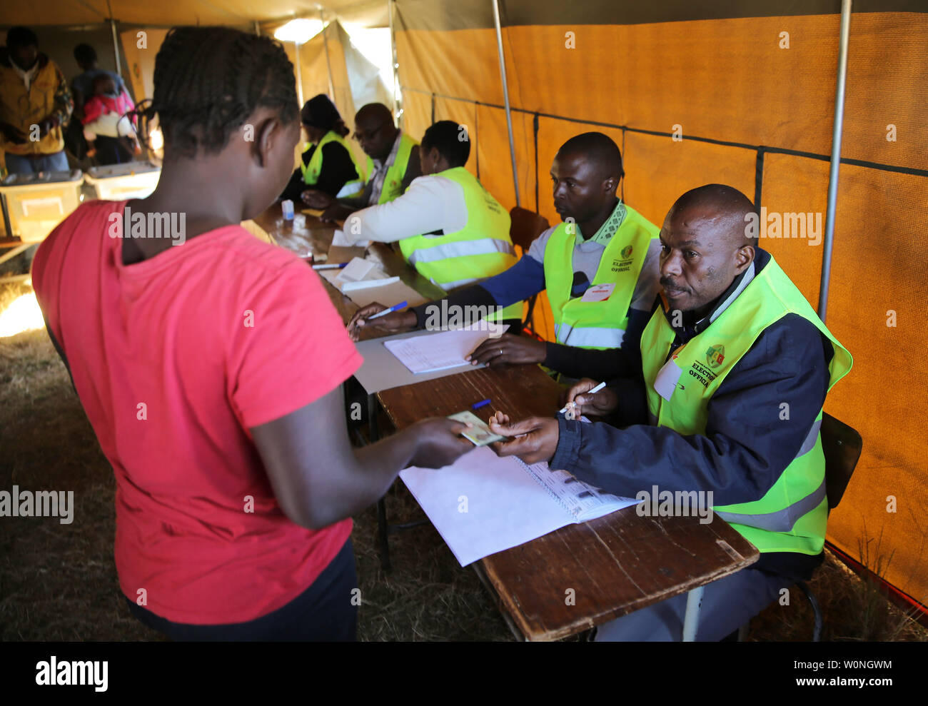 A woman has her ID checked in order to cast her vote at a