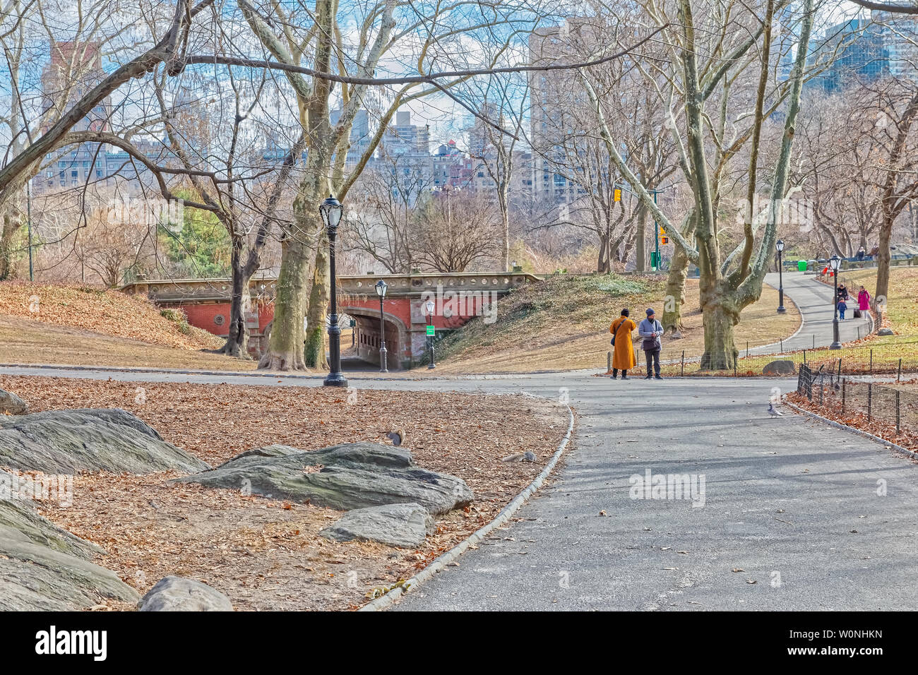 NEW YORK, USA - JANUARY 15, 2018: People walking by the red brick Driprock Arch bridge in Central Park winter season. - Stock Image