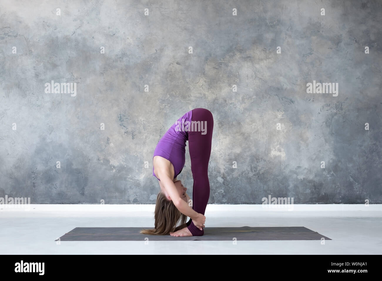 Woman doing head to knees, uttanasana exercise, Standing forward bend pose Stock Photo